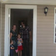 Homeowners standing in doorway of new home